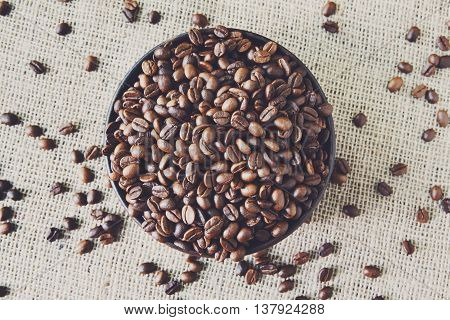 Burlap texture with coffee crop in a bowl background, plenty of robusta beans in plate closeup. Sack cloth canvas with copy space. Scattered seeds at hessian textile, sof toning