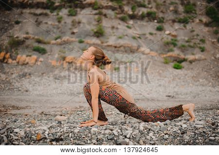 Young woman doing yoga on a rocky seashore upward facing dog pose. ashwa sanchalanasana