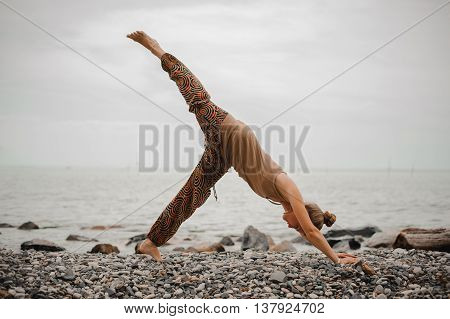 Young woman practicing yoga in downward facing dog pose on beach near the sea