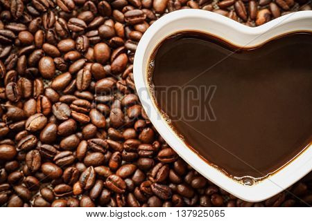 Coffee. A cup of coffee with a heart shape surrounded by coffee beans. Love drinking coffee concept