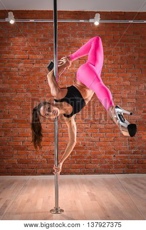Pole dance, fit woman posing with pylon.