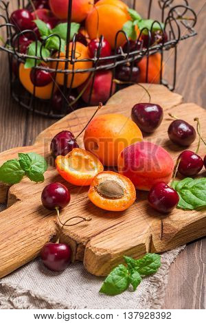 Summer fruits in metal basket on dark wooden table. Apricots and cherries on rustic  background
