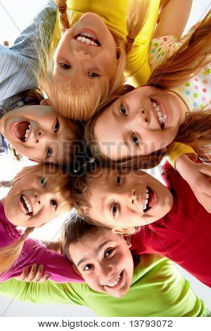 Team of happy kids embracing each other