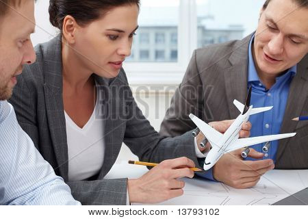 Three engineers looking at a small model of a plane