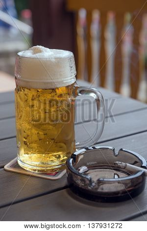 Beer mug and cigarette on table in a pub