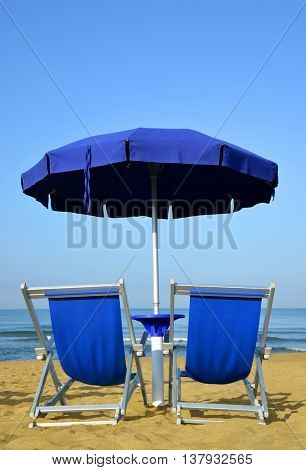 Sun loungers and umbrella on a sandy beach. Vacation concept.