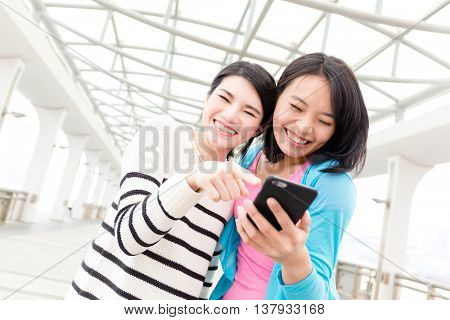 Friends using mobile phone together