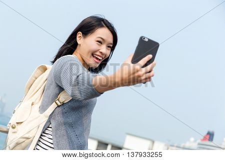 Woman taking photo by mobile phone in Hong Kong