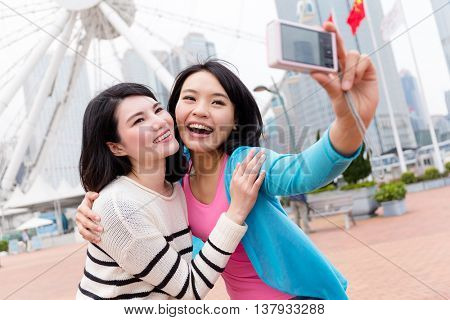Excited Friends taking photo by camera together in Hong Kong