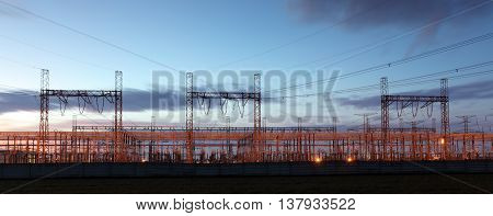 distribution substation silhouetted against dusk sky electricity background