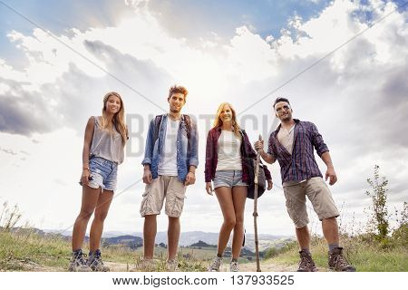 Group Of Young Hikers Walking Toward The Horizon Over The Mountain