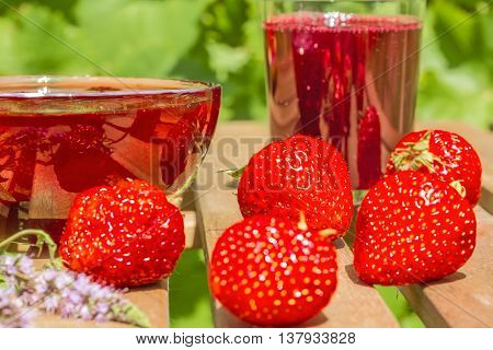 Red ripe strawberries strawberry jam in a glass outlet and juice in a glass on a wooden table in the summer garden on a blurred background of green leaves macro. Selective focus