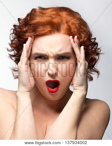 Portrait of a beautiful young woman with red hair on a white background with his arms raised to the head