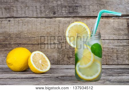 Summer fruit drink on wooden background. Cold lemonade with ice. Detox citrus infused flavored water. Refreshing summer homemade cocktail with lemon. Fresh lemon and lemonade on wooden background