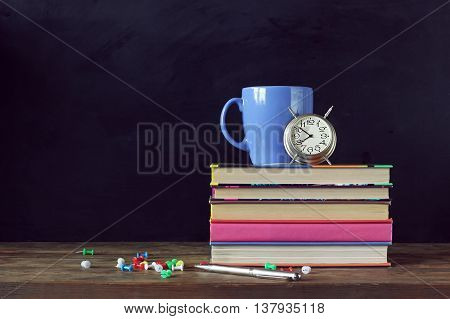 Back to school. A stack of books alarm clock Cup and stationery on the table in the background of a school blackboard.