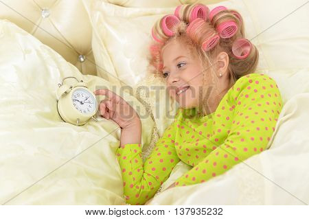 Happy cute little girl in hair curlers awaked up with clock