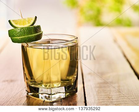 Alcohol drink. On wooden boards is glass with alcohol green transparent drink. A drink number seventy cocktail green tea with slice lime. Country life. Light background.