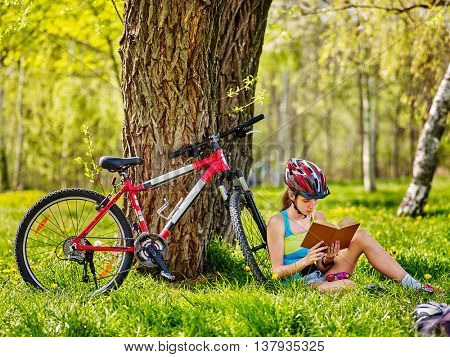 Bikes cycling girl. Girl rides bicycle. Girl in cycling read book on rest near bicycle. Cycling wearing helmet. Cyclist looking at book.
