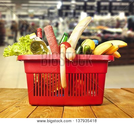 Brown table and blurred supermarket and basket with products on background