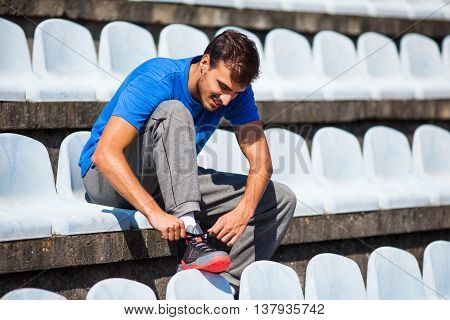 Young man is tying a shoelace before jogging.