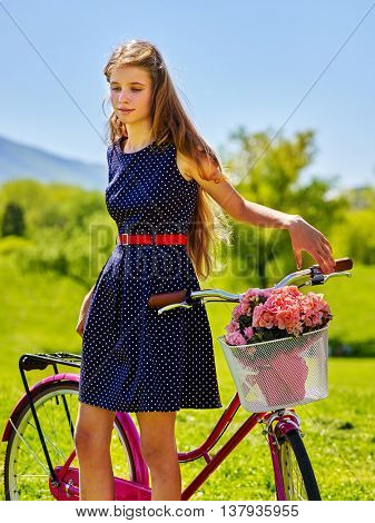 Bikes bicycle girl. Teenager girl wearing blue polka dots dress looking down on green grass keeps bicycle with flowers basket. Lot of green tree and grass in park.