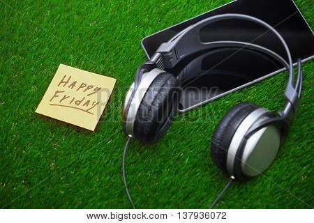 Happy Friday text on sticky note on a grass with headphones and digital tablet