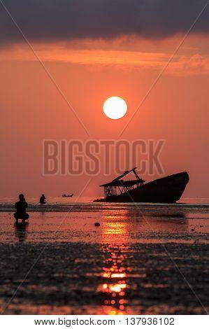 wreck boat sun rising sky and photographer at phuket thailand