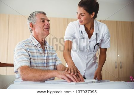 Nurse helping senior man with braille in a retirement home