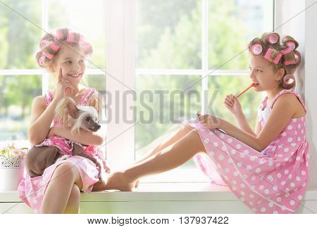 Cute  tweenie girls  in hair curlers  with dog  at home