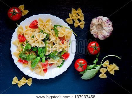 italian type pasta called farfalle butterflies rucola and little tomatoes