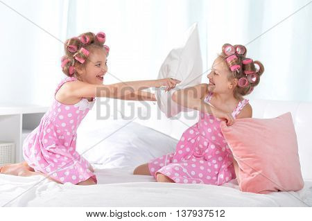 Cute  tweenie girls  in hair curlers playing with pillows with  at home