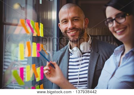 Portrait of business people smiling while standing by sticky notes stuck to glass in office