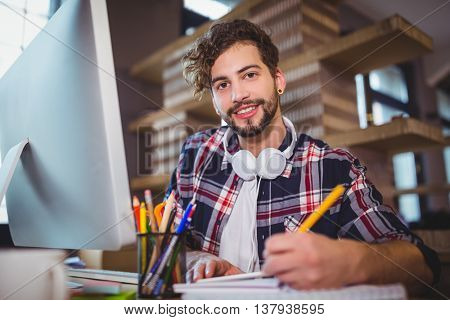 Portrait of creative businessman writing in spiral notebook at computer desk