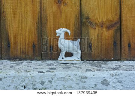 white porcelian goat on fundation and yellow wall