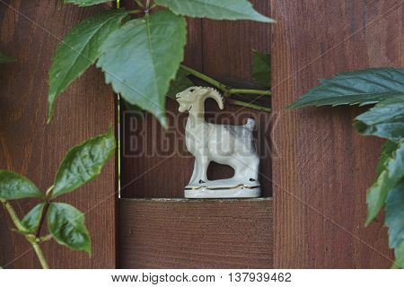 white porcelian goat on red board fence