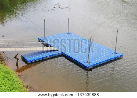 Bright blue plastic dock for parking boat or rafting in the river