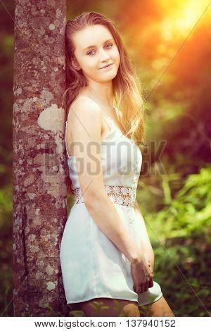 Beautiful teen girl standing by tree