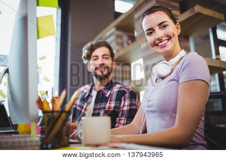 Portrait of happy businesswoman sitting by male coworker at computer desk in office