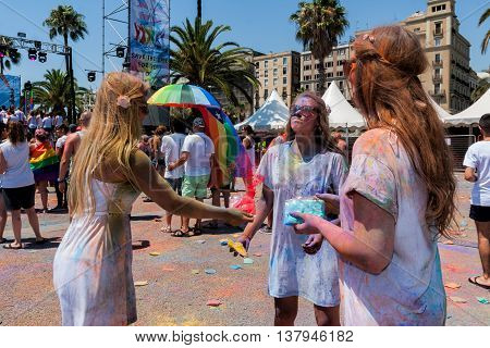 BARCELONA SPAIN - JULY 9 2014: Girls painted each other on Holi festival at Escenario del Moll de la Fusta.