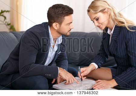 Young manager flirting with businesswoman in office review contract