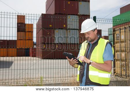 Logistics Manager At Container Transhipment Plant, With An Electronic Tablet