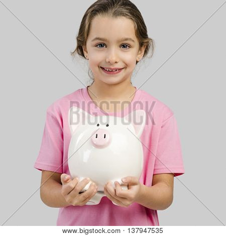 Cute little girl holding a piggybank with her savings