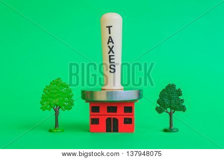 a meat mallet with the word taxes compresses a crushing home representing the tax burden that exists on the house