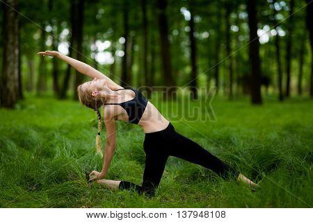 Nature yoga session in beautiful green polish woods between trees. Half camel pose: Ardha Ustrasana