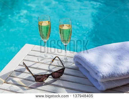 Two glasses of sparkling champagne on a white wooden table next to the swimming pool in summer.