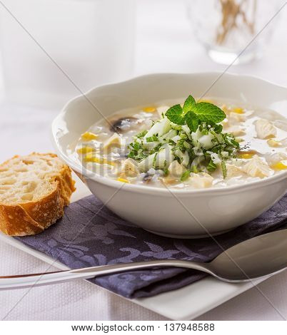 A bowl of rice chicken and corn soup served with raw onions parsley and mint leaves.