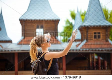 Young traveling woman in country taking photos. Active time on nature on the weekend.