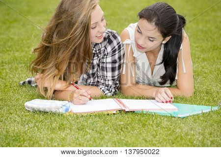 Teenage students lying on the grass and study together