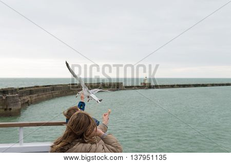 DOVER ENGLAND - OCTOBER 24 2015: Two unknown children feeding seagulls on a ferry boat in the port of Dover