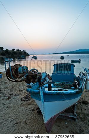 Fishing boat on a beach in front of ruins of a roman fortress at sunset, Sithonia, Greece